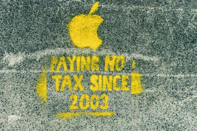 Street art with Apple logo and text reading Paying No Tax Since 2003